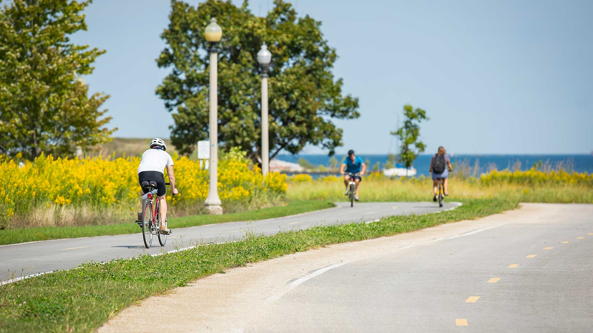 A few people ride bikes on a path near Lake Michigan. The lake is ahead; grass and trees line the path along the left.