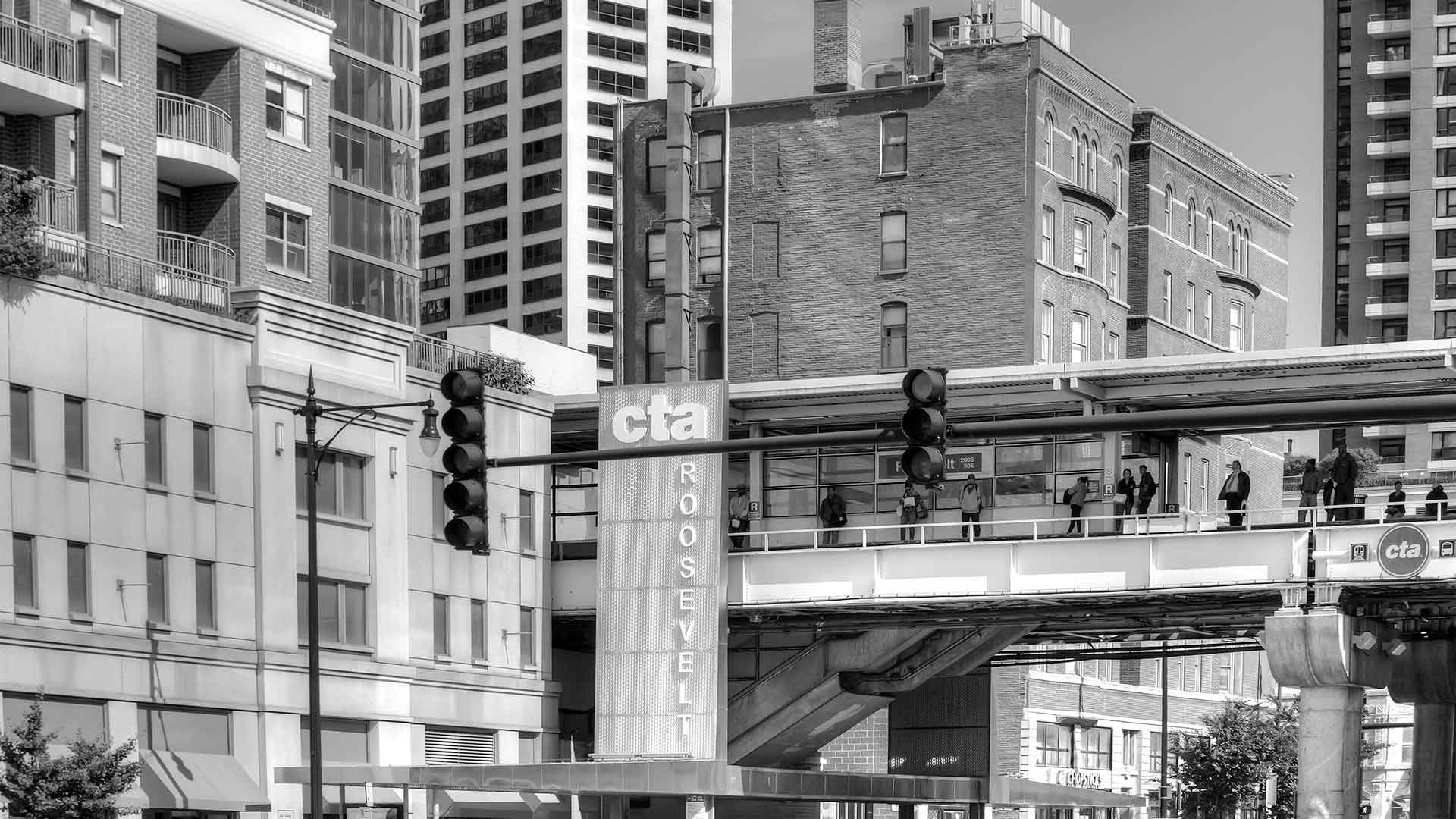 The CTA Roosevelt elevated train stop crosses over Roosevelt road with tall buildings in front and behind it.