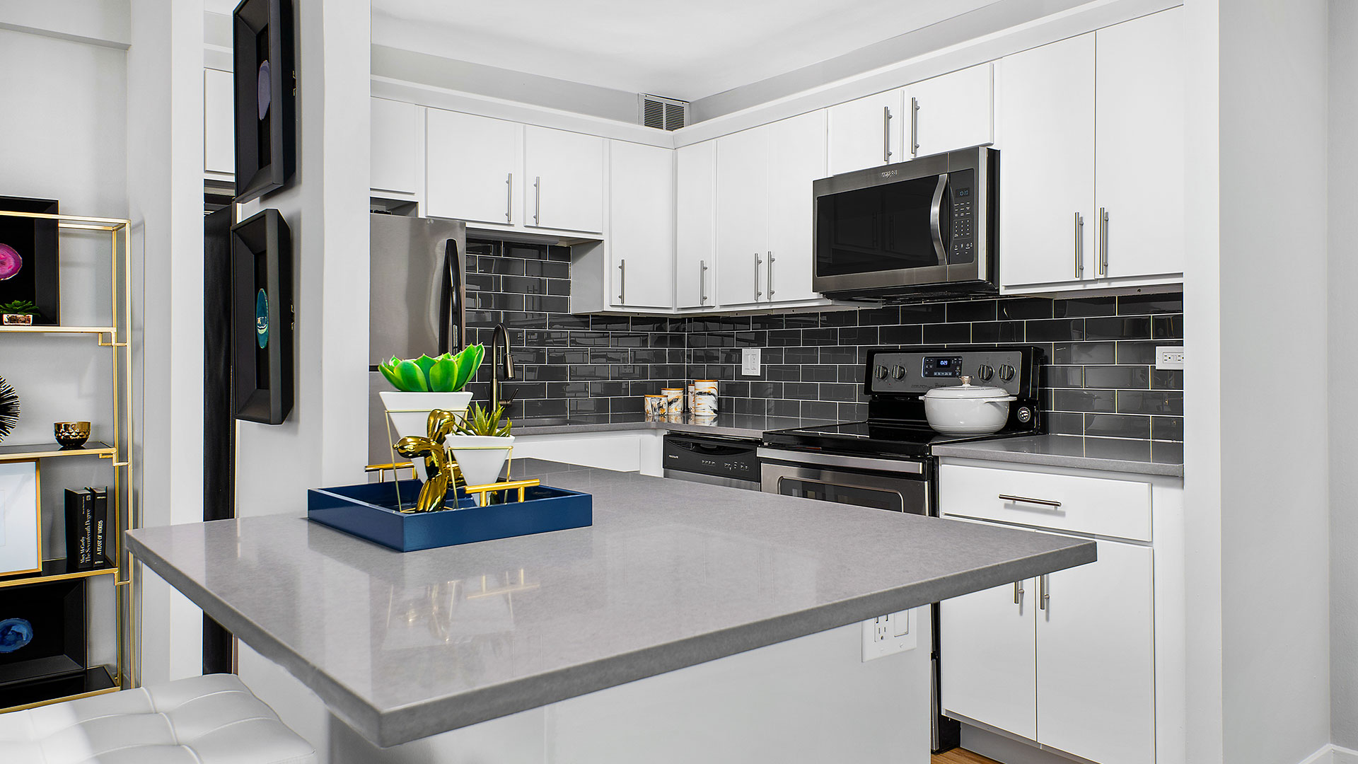 Looking across the kitchen island at a residence kitchen at Eleven Thirty. The cabinets are white with a black, subway tile backsplash. The stainless oven and microwave or in the middle with the refrigerator to the left.