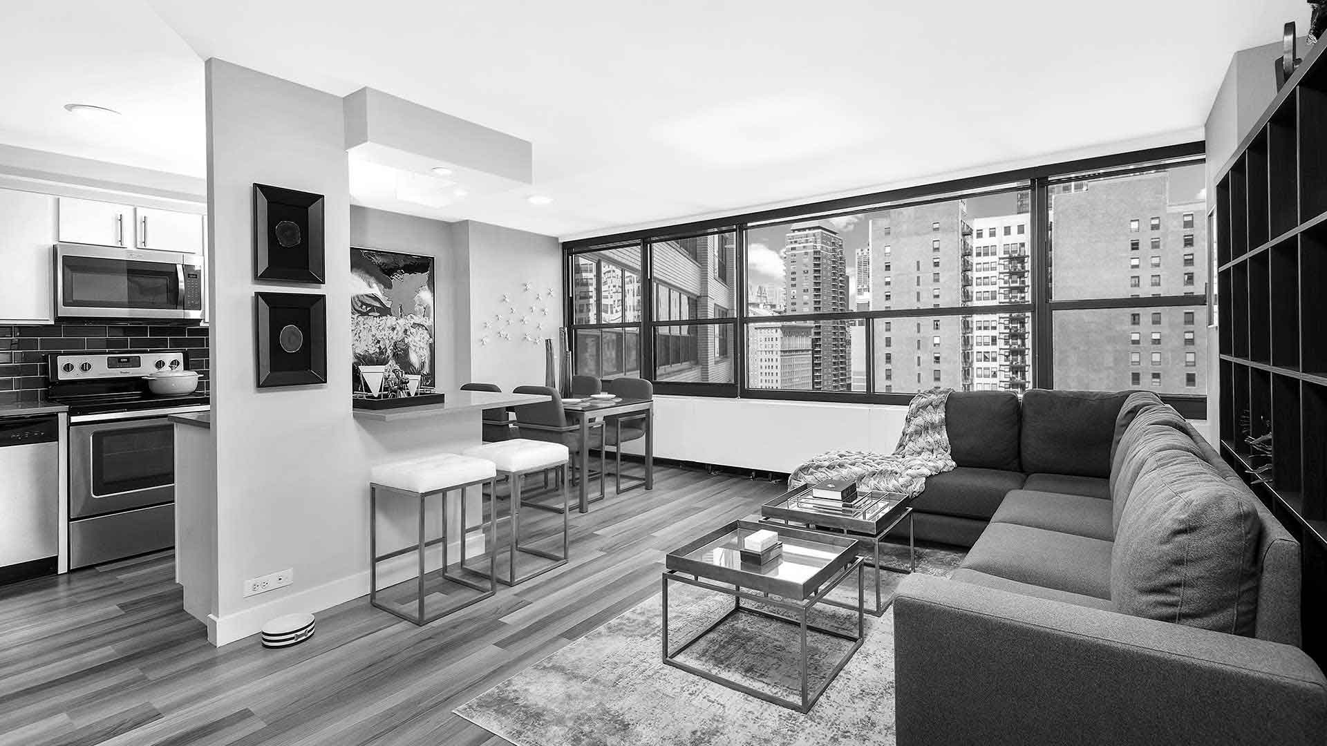 A living room in a residence at Eleven Thirty. A couch goes off to the right leading the windows that show the city outside. The kitchen is off to the left and a dining area further back by the windows.