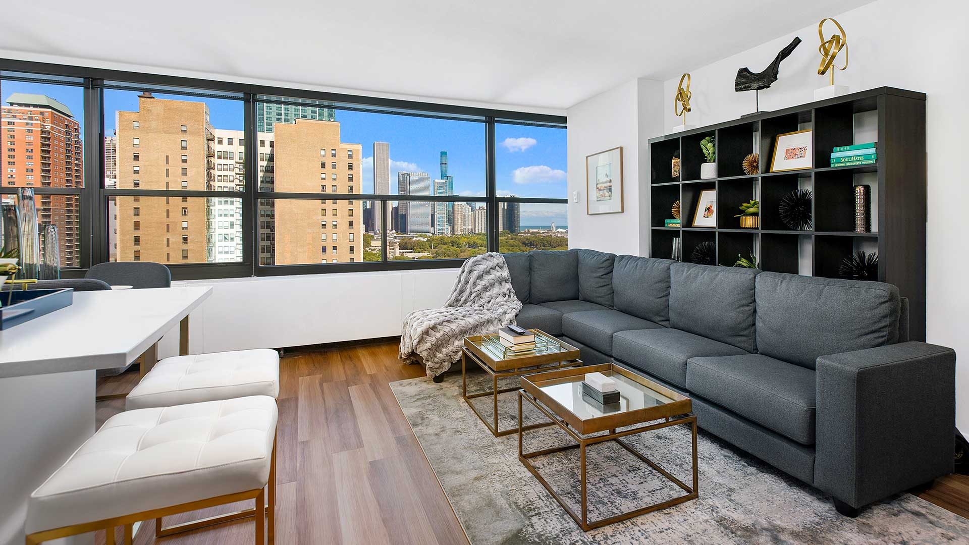 A living room in a residence at Eleven Thirty. A couch lines the right wall with a book shelf behind it. Chicago buildings, Grant Park and Lake Michigan can be seen out the windows.