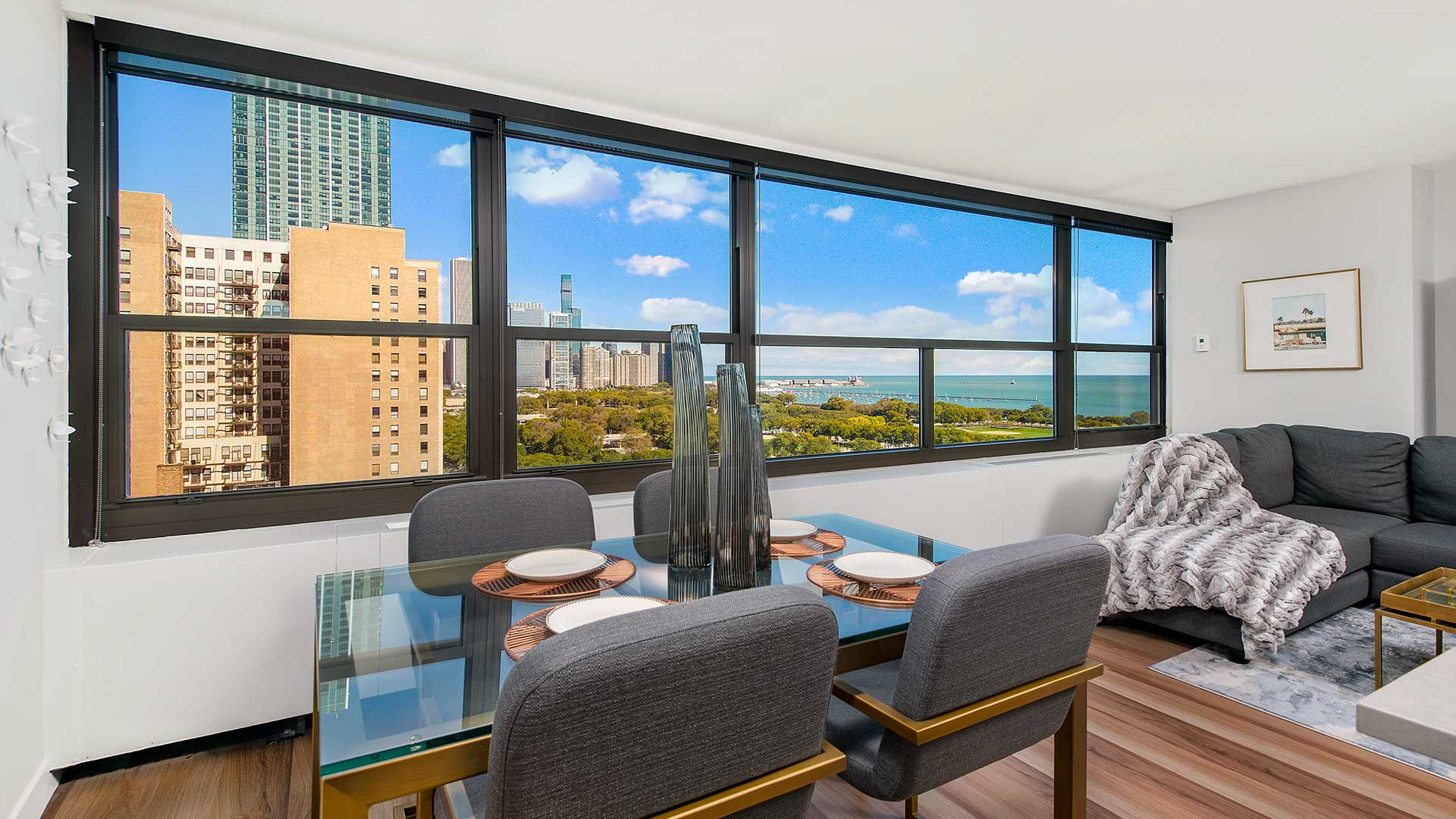 Looking across the dining room, out the windows of a residence at Eleven Thirty. Buildings in the Chicago skyline are seen outside to the left, while Grant Park and Lake Michigan are seen to the right.