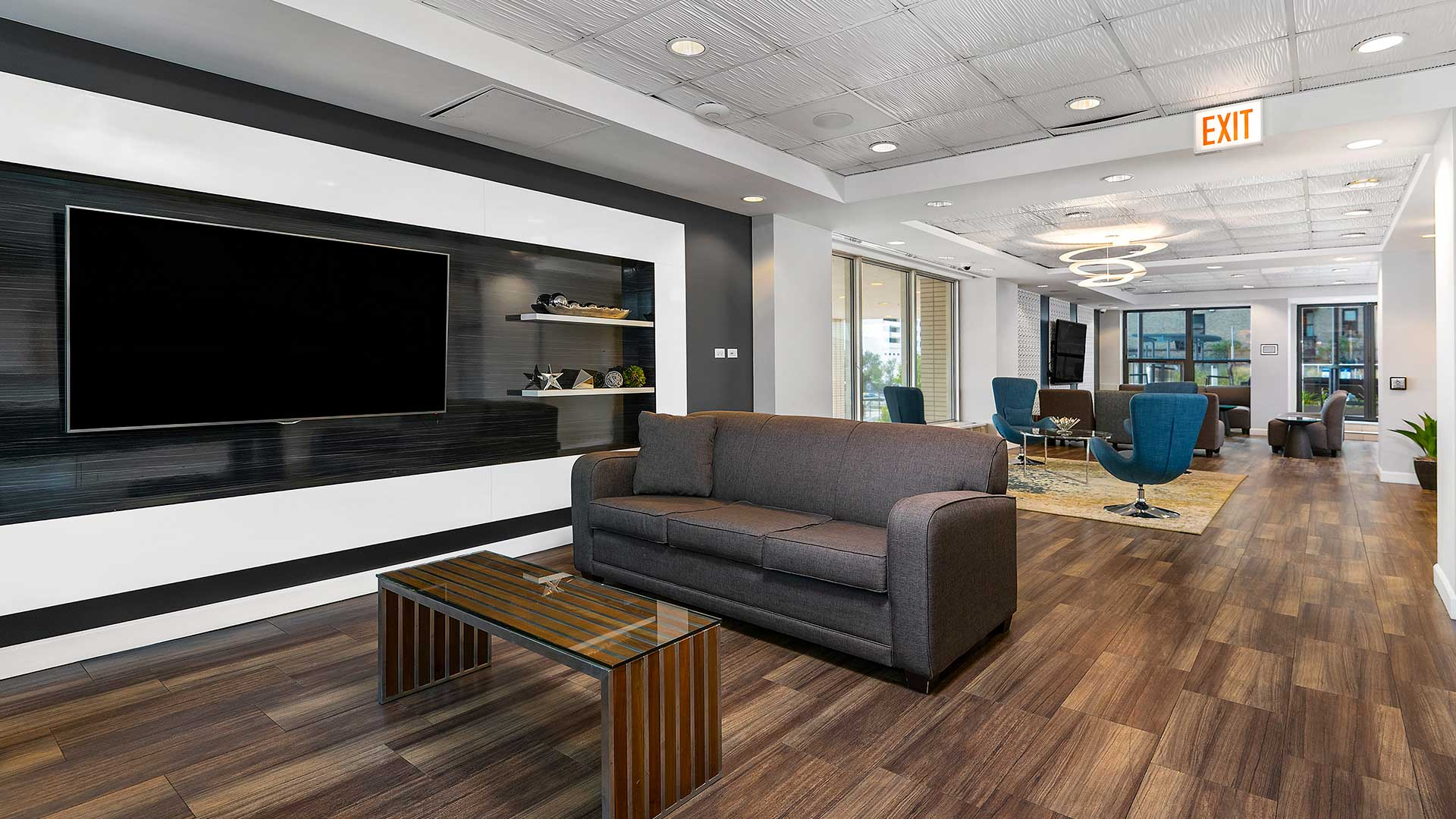 The community room at Eleven Thirty. A couch and coffee table sit beside a large television in the foreground. Additional lunge furniture and another television are the in background.