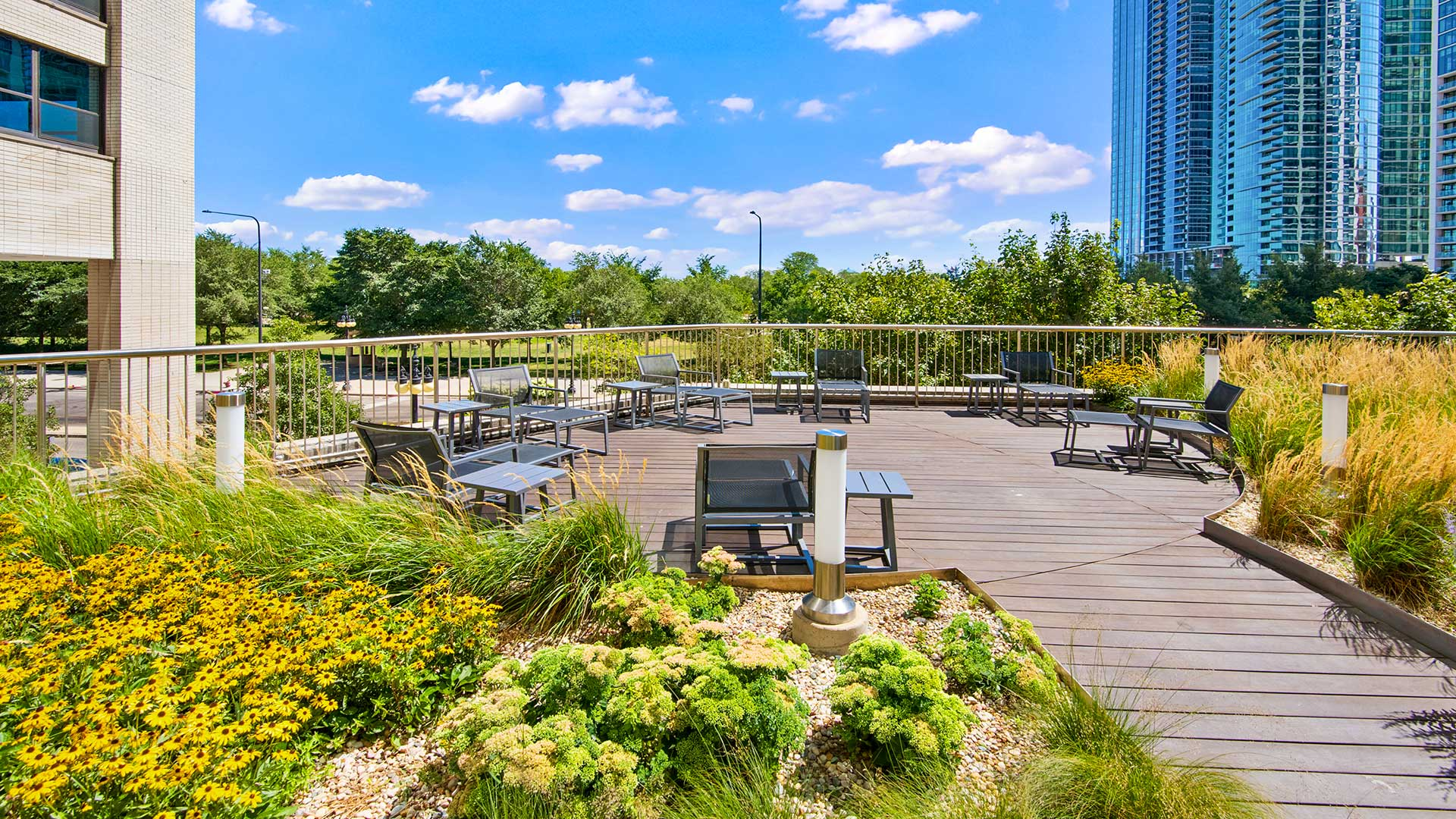 Pretty flowers surround a sitting area on the Eleven Thirty sundeck. Grant Park is seen over the balcony on a sunny day.